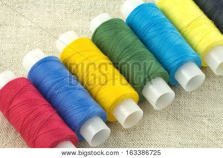 Row of color threads spools on beige fabric close up diagonal view