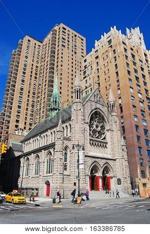 New York, United States of America - September 14, 2014. Holy Trinity Lutheran Church at W 65 st in New York, with high-rise buildings in the background, city traffic and people.