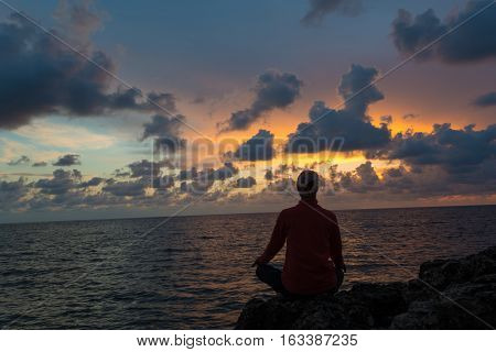 Woman sits as yogi against beautiful sunset over sea background.