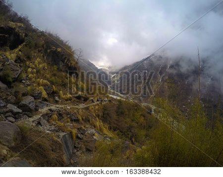 Mountain landscape. Fog in the mountains. Himalaya afternoon in severe natural environment. Everest trekking path in Sagarmatha National Park. Outdoor travel and sport. Mountain river valley