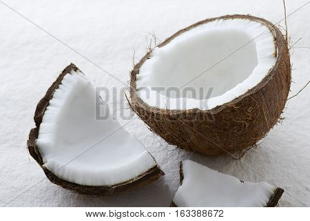 Close up of a whole coconut cracked open on a textured white surface.