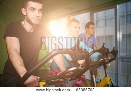 Young people engaged on stationary bike in gym