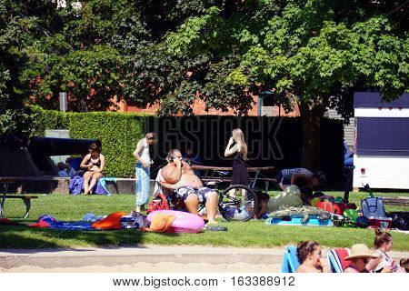 HARBOR SPRINGS, MICHIGAN / UNITED STATES - AUGUST 3, 2016: People enjoy sunbathing at the Zorn Park Public Beach near downtown Harbor Springs.