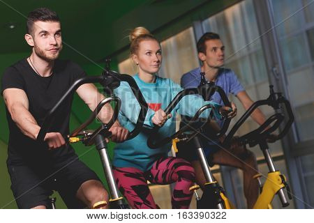 Young athletes on stationary bike in fitness center in sport clothes