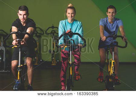 Three athletes on stationary bike at sports center