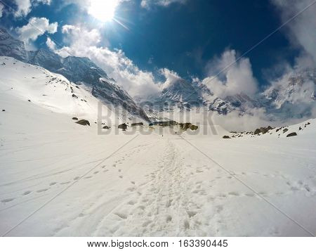 Winter landscape with sun. Experimental sun light view with snowy path and rocky peaks of Himalaya. Blue sky with fluffy clouds. Outdoor travel and extreme sport. Clean ecologic environment
