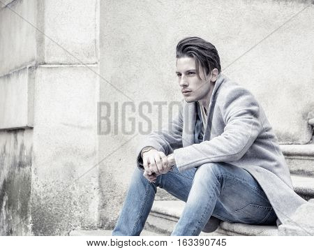 Elegant attractive young man outdoor wearing wool coat, in European city