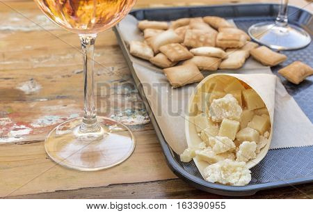 A photo of a cucurucho, a paper cone with a selection of cheeses, with a glass of wine. Market food in Spain