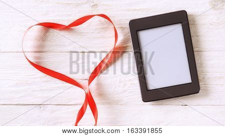 ebook and red tape in the form of heart copyspace