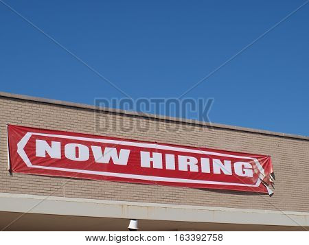 A now hiring sign hangs on the side of a building in north Dallas.