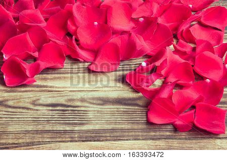 scattered petals of red roses on a wooden brown background