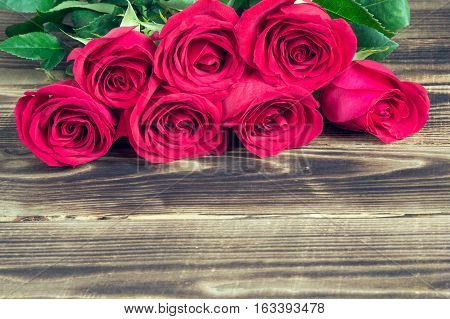 red roses in a bouquet on a wooden brown background