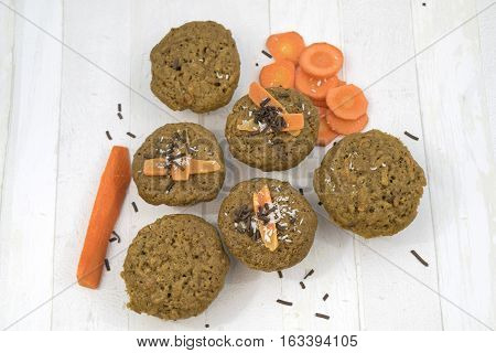 Homemade carrot muffins on a white wooden background. Muffins with carrots and chocolate sprinkles. Top view