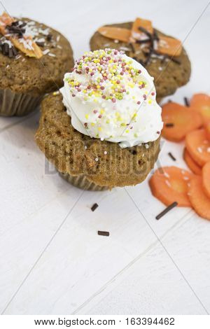 Homemade carrot muffins on a white wooden background. One big muffin with whipped cream and colorful and chocolate sprinkles. Top view