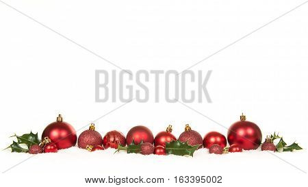 Row of red christmas ball decorations and green holly ilex in the snow on a white background