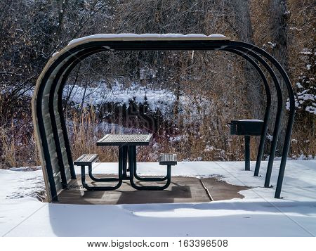 Snowy Covered Park Bench And Grill