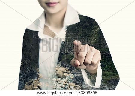 Female hand of business woman pointing index finger at viewer or camera double exposed technic with mountain landscape image white background