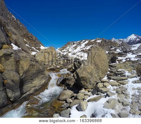 Mountain landscape with river. Trek to mountain Sagarmatha. National Park in Himalaya. White water current snow peaks and rocks landscape severe winter in cold climate. Nepal ecologic travel