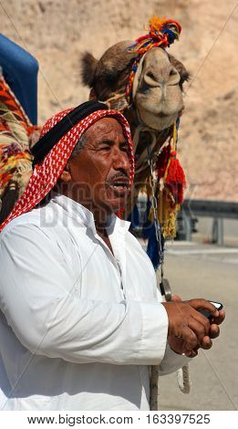 DEAD SEA LEVEL ISRAEL 10-29-16: Portrait of a Bedouin and his camel. Negev Bedouin are traditionally pastoral nomadic Arab tribes living in the Negev region in Israel.