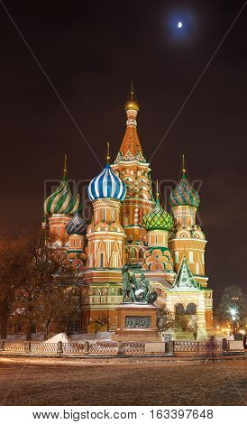 Saint Basil's Cathedral at the Red Square in Moscow by a winter night illuminated by streetlight with Kremlin wall and cloudy sky with moon