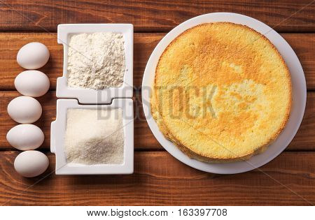 Round homemade golden biscuit cake on a plate flour sugar and eggs on wooden table. Ingredients for the cake. The cake and the ingredients from which it was prepared