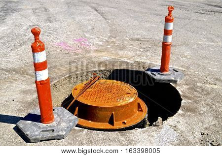 Orange warning cones surround a sanitary sewer construction project