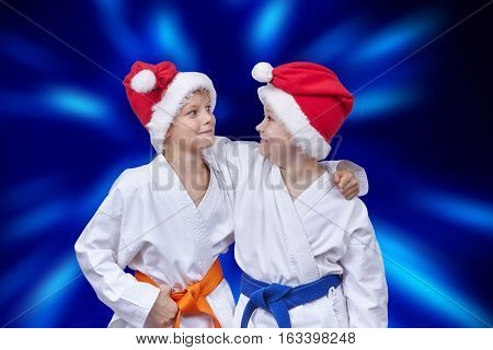 Two athletes in caps of Santa Claus on a background of blue radiance