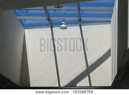 Modern building lighting with round lamp and roof windows. Concrete walls with sun light and shadows. Hi-tech ceiling for shopping mall or museum. Summer blue sky view through transparent glass roof