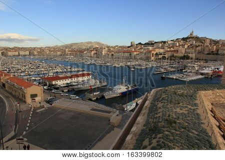 the French city of Marseille. It depicts a beautiful yacht, sailing boat, blue sea. In the background a small house, the hills on one of them stands the Church Notre-Dame de la Garde