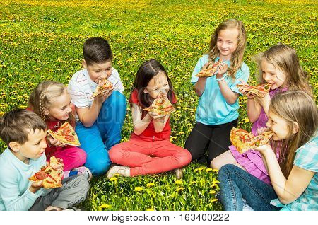 Group of happy children eating pizza outdoors