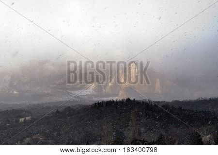 View on heavy snowfall, mountain  and forest under snow. Ice storm, snowstorm,  blizzard. Winter landscape.