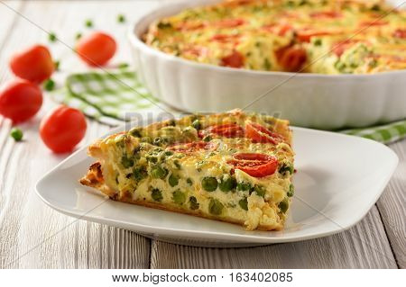 Vegetarian quiche with green pea, tomatoes and cheese.
