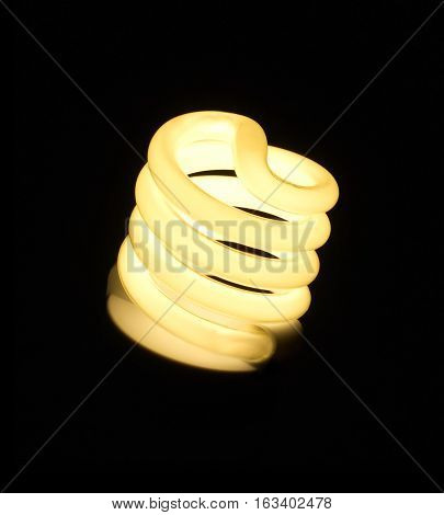 Energy saving bulb spiral brightly lights isoalted on black close up