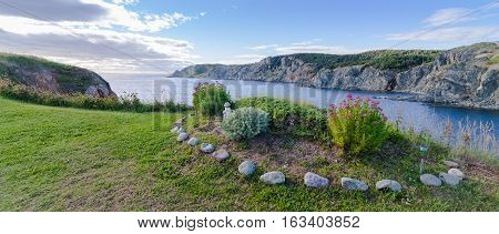 Garden by the sea in Twillingate, Newfoundland.     Simple flower and shrub garden in summer at the top of a cliff near the ocean's edge in a Newfoundland village.