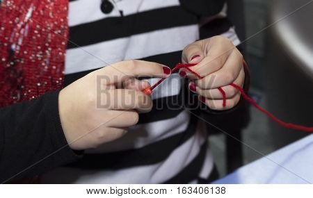 people and needlework concept - girl hands knitting with crochet hook and red yarn