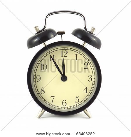 Alarm clock in black case and beige clockface shows 5 minutes to twelve isolated on white close up