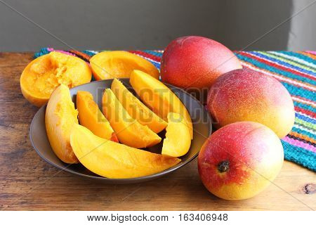 Colorful whole and sliced mangos on wooden table with colorful place mat