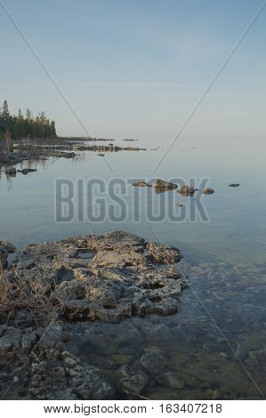 Dead calm afternoon image of clear lake huron water and limestone rocks along shoreline.