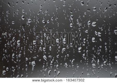 The image shows the pane only and background is darker and the raindrops lighter. The rain drops are even over the glass
