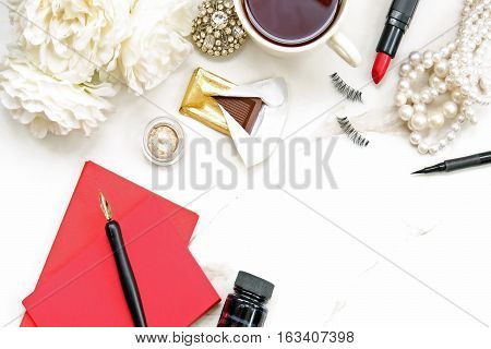 White elegant make up table with jewelry, make up, jewelry and stationary.
