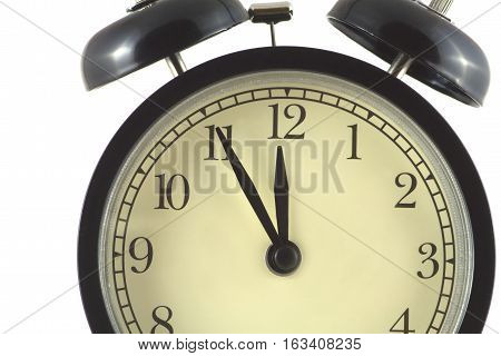 Alarm clock fragment in black case and beige clock face shows 5 minutes to twelve isolated on white close up
