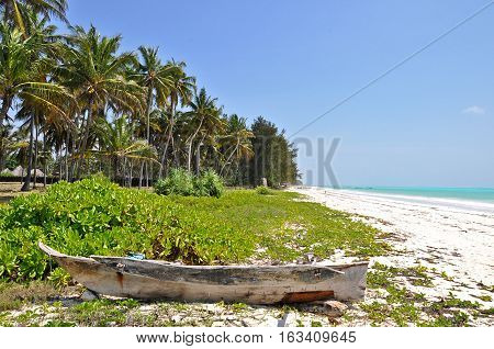 An old wooden boat lost in a paradise beach