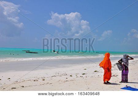 Two women walk ashore in a paradisiac beach