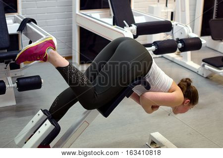 Young woman working out her back muscles and gluteus at the gym.