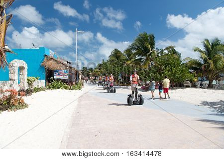 Costa Maya Mexico - February 01 2016: people rolling on electric sport transportation of segway in helmets on road sunny outdoor