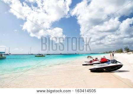 Bridgetown Barbados - December 12 2015: sport transportation of jet ski on sandy beach at sea or ocean coast with people sunny outdoor on sky background