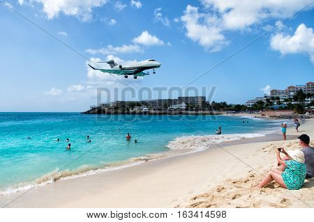 St Maarten Kingdom of Netherlands - February 13 2016: beach crowds observe low flying airplanes landing near Maho Beach on island of St Maarten in the Caribbean