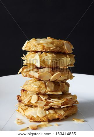 Stacked almond cookies on a white plate