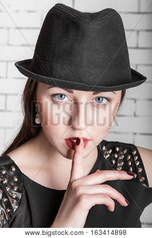 Close-up portrait of young woman in hat placing finger on lips gestures silently quiet shhhhh secret facial expression human emotions signs and symbols