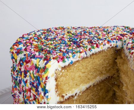 White cake covered in white frosting and rainbow sprinkles with a slice missing